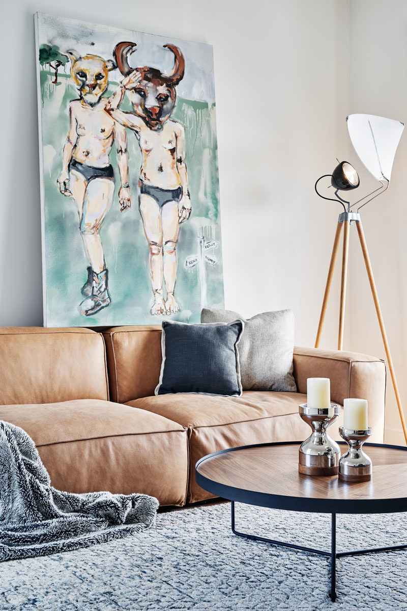 Living Room Ideas - In this modern living room, furnishings have been kept relaxed and welcoming, with a plush couch, neutral walls, and a tripod floor lamp with a diffuser to create soft lighting. #LivingRoom #LivingRoomIdeas #ModernLivingRoom