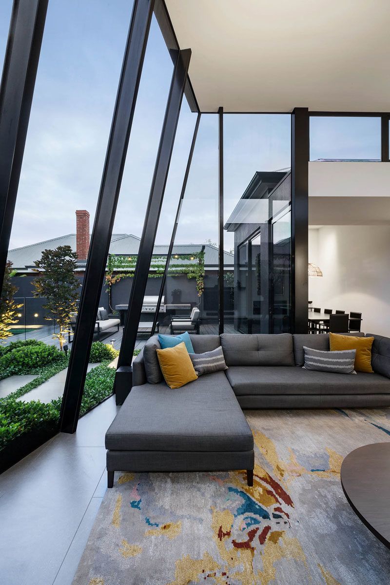 Window Ideas - At the end of the hallway in this modern house, there's an open plan living room, dining room, and kitchen, with soaring ceiling heights and floor-to-ceiling windows, that introduce a sense of space, light and scale to the residence. #ModernInterior #WindowIdeas #WindowDesign #LivingRoom #LivingRoomIdeas