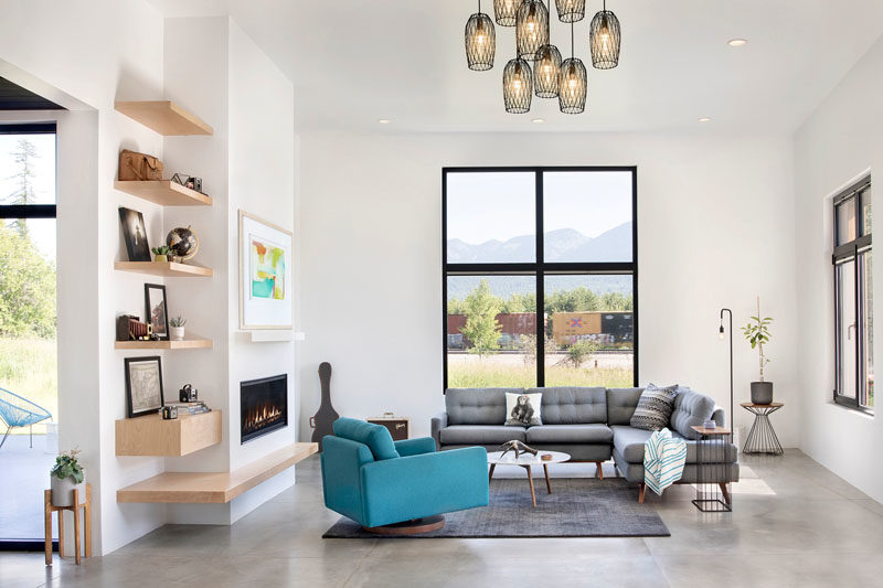 Living Room Ideas - High ceilings in this living room help to create an open and airy interior, while the windows frame the landscape, and a built-in fireplace helps keep the room warm on a cool night. #LivingRoomIdeas #Fireplace #LivingRoom #Windows