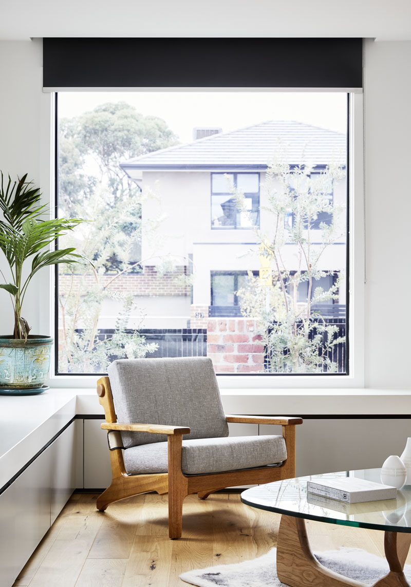This large black-framed window provides views of the front garden and the street, while underneath the window, cabinets have been built to wrap around the corner of the living room. #Window #LivingRoom #Storage
