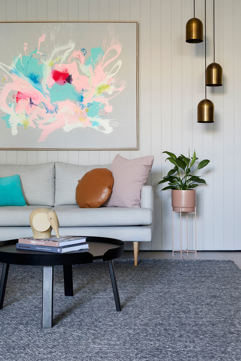 Living Room Ideas -This modern living room takes advantage of the white walls by placing a large colorful abstract art piece above the couch, while three metallic pendant lights hang above a plant on a plant stand. #LivingRoomIdeas #LivingRoom #Decor #InteriorDesign
