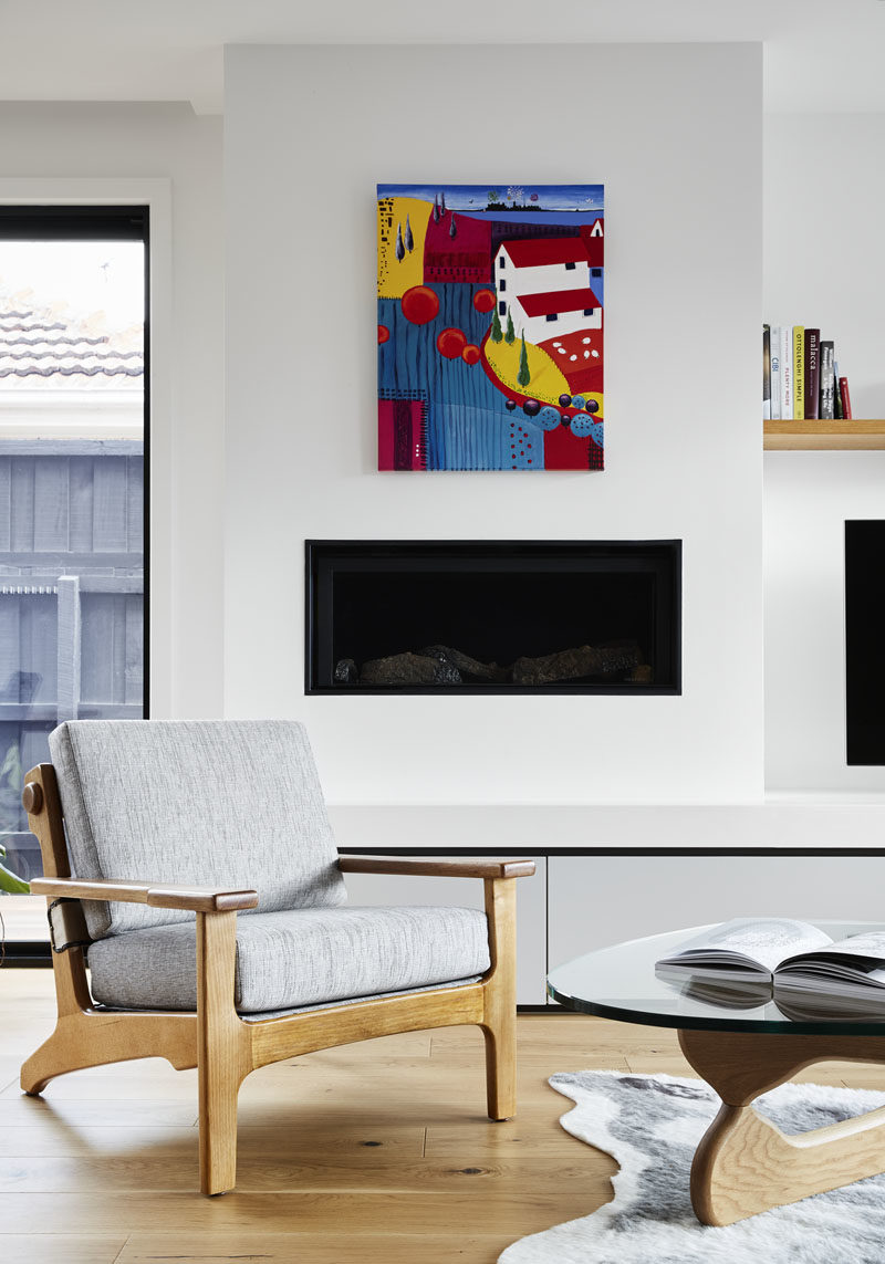 A bright piece of colorful art hangs above a built-in fireplace in this modern living room. #Fireplace #LivingRoom #ModernInteriorDeisgn