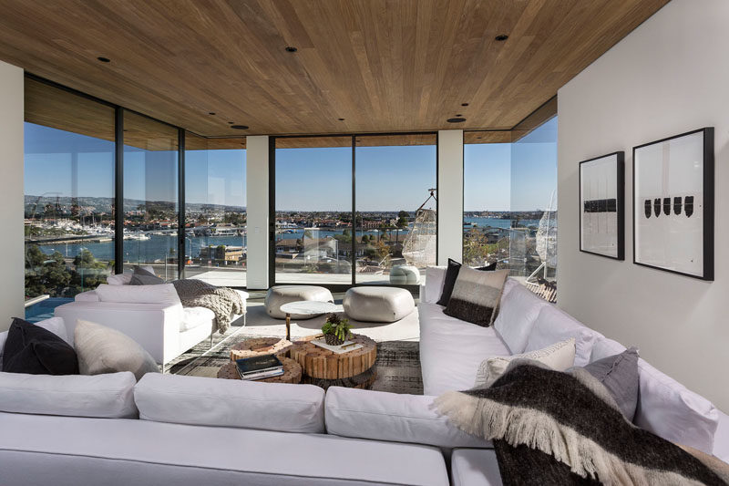 Living Room Ideas - This modern and mostly white living room has glass walls to take advantage of the surrounding views. #LivingRoom #WhiteLivingRoom #GlassWalls #WoodCeiling