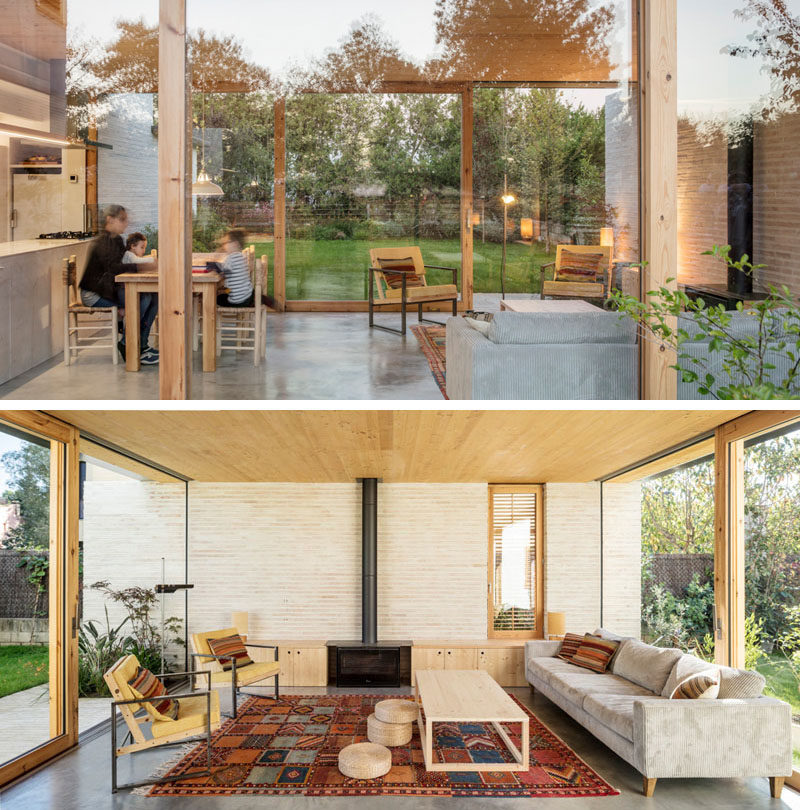 This modern house has an open floor plan with the living room enjoying a fireplace with built-in storage on either side. #The two glass walls have sliding doors that open to the garden. #LivingRoom #Fireplace #GlassWalls