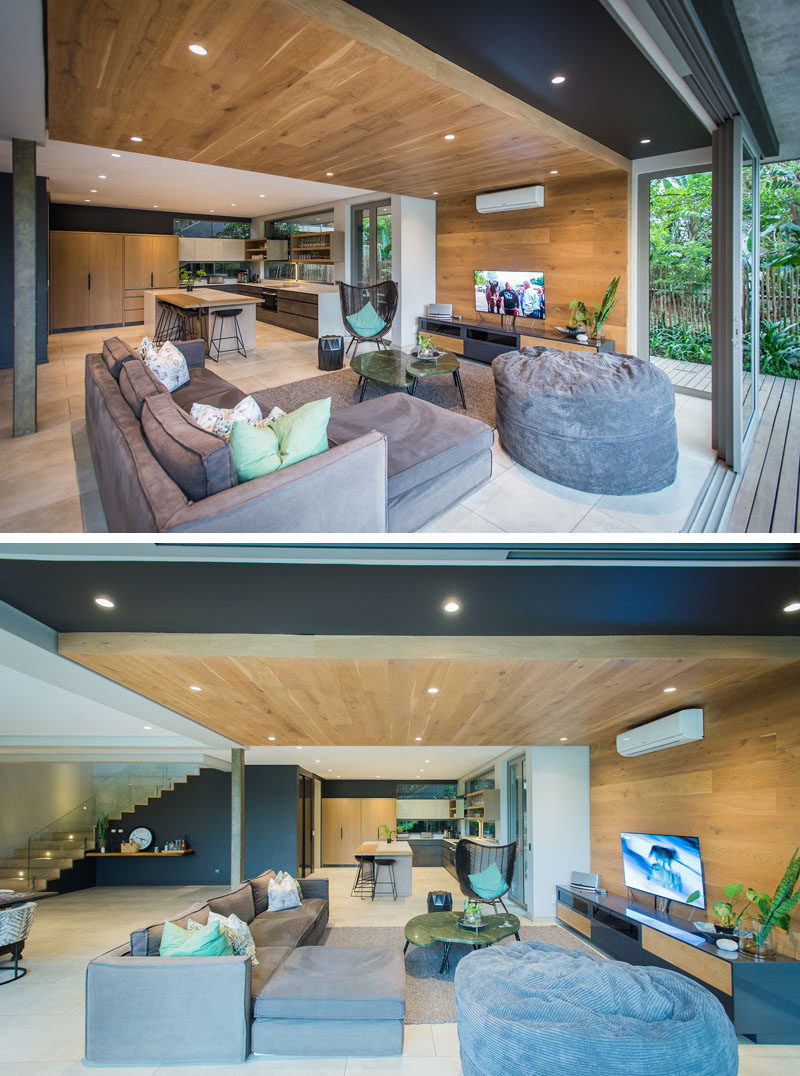 Wood elements, like the wood ceiling that wraps around and down onto the wall in the living room, bring a natural touch to the interior of this modern house. #WoodCeiling #WoodAccent #ModernInterior #ModernHouse #LivingRoom