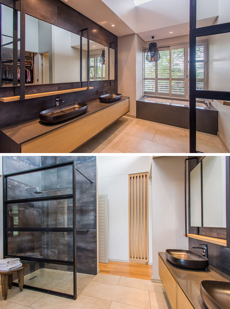 In this modern master bathroom, a long wood floating vanity has plenty of room for two basins, while the built-in bath has been positioned underneath the window, and the shower is separated from the rest of the bathroom by a black-framed glass wall. #ModernBathroom #BathroomIdeas #BuiltInBathtub