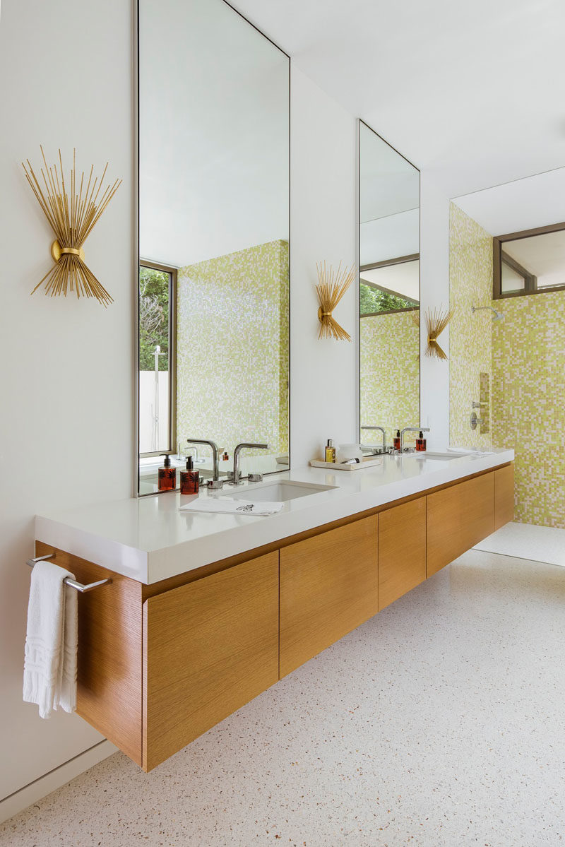In this modern master bathroom, tall mirrors reflect the light from outside, while delicate sconces reflect the mid-century design of the house. #ModernBathroom #BathroomDesign #BathroomIdeas