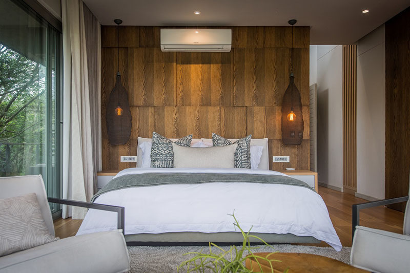 In this modern bedroom, a paneled wood accent wall showcases the grain, while delicate basket-like pendant lights hand on both sides of the bed. #BedroomDesign #BedroomIdeas #WoodAccentWall