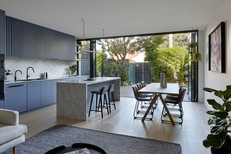 The rear of this modern house is organized in an open plan layout, with the living room, dining area, and kitchen all sharing the same space. Folding glass doors connect the interior with the yard. #InteriorDesign #OpenPlanLayout