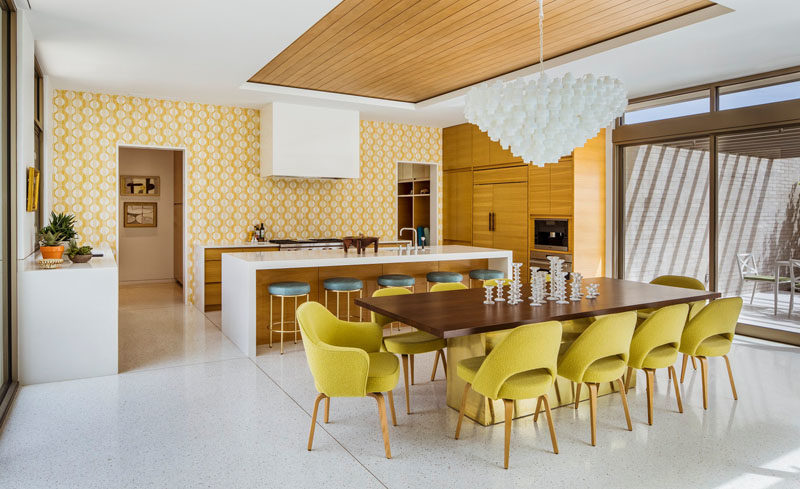Pastel yellow wallpaper in this kitchen complements the dining chairs, and adds a pop of color to the interior. #Kitchen #Yellow #InteriorDesign