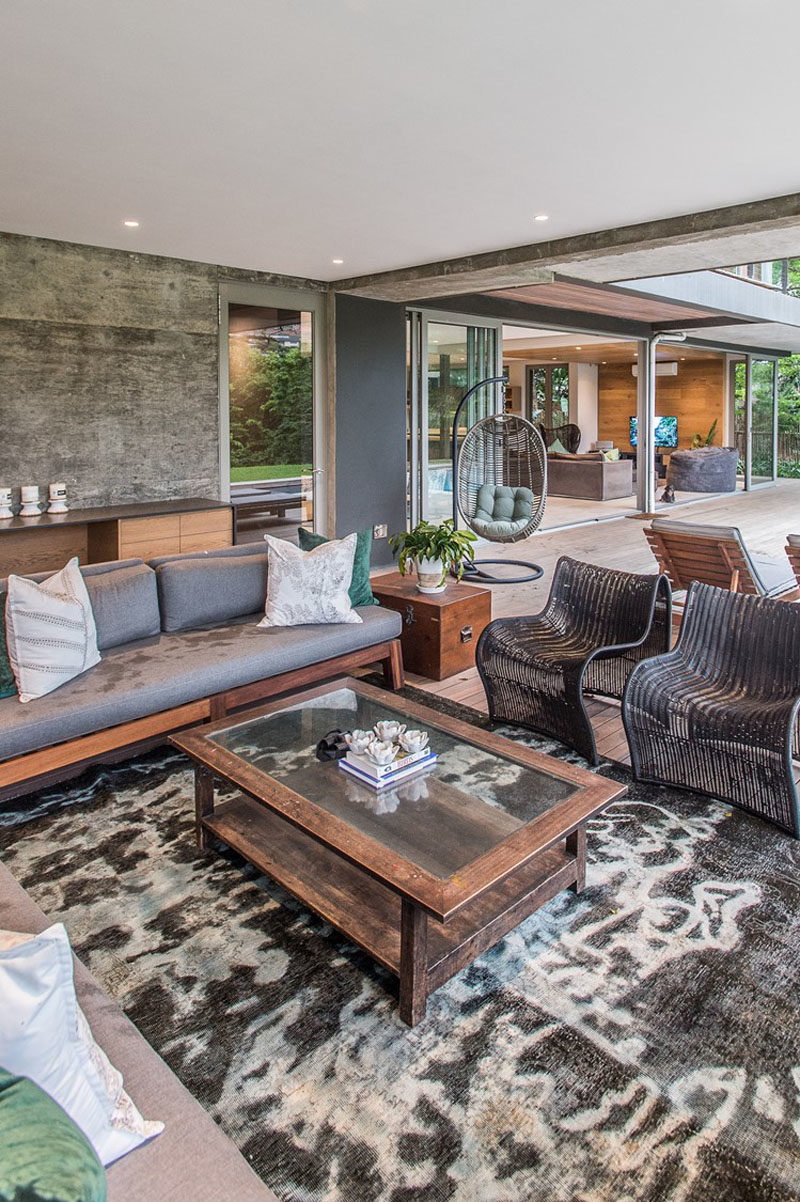This modern house has a covered outdoor living room with multiple seating options. #OutdoorLivingRoom #InteriorDesign