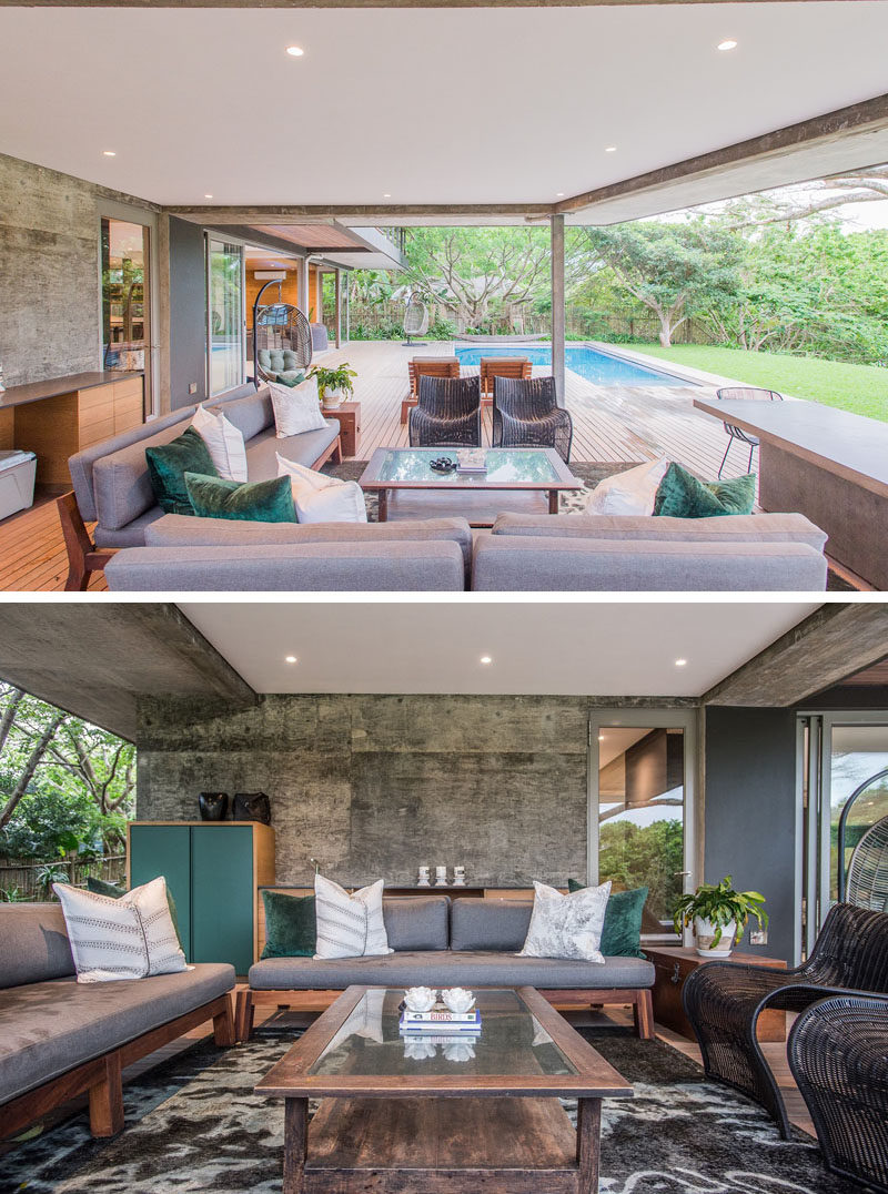 This modern house has a covered outdoor living room, fully furnished with couches, chairs, storage, and a table.  #OutdoorLivingRoom #OutdoorSpace