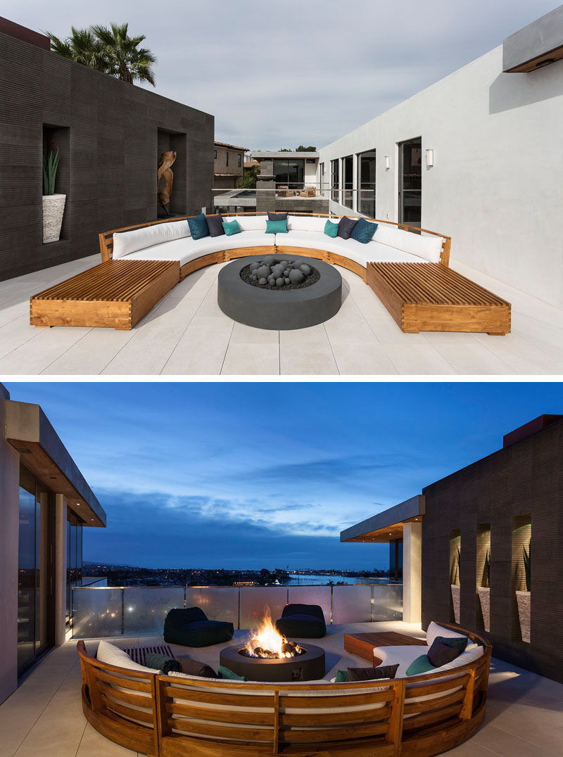 This outdoor entertaining area has a curved wood couch with white upholstered cushions, and a freestanding firepit. #OutdoorLounge #CurvedOutdoorFurniture #Firepit