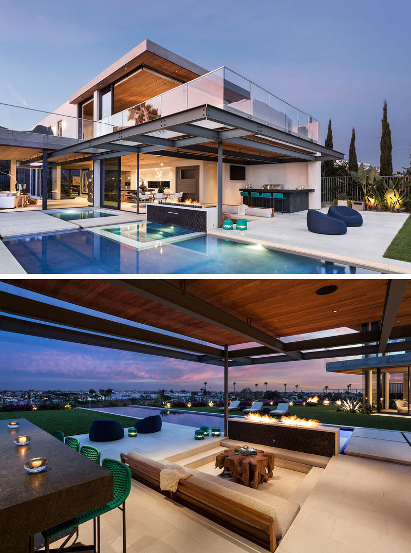 The interior of this modern house has glass walls that open to an outdoor kitchen / bar, and a sunken lounge. An outdoor fire separates the sunken lounge from the swimming pool. #OutdoorSpace #SunkenLounge #OutdoorKitchen #OutdoorBar #OutdoorFireplace