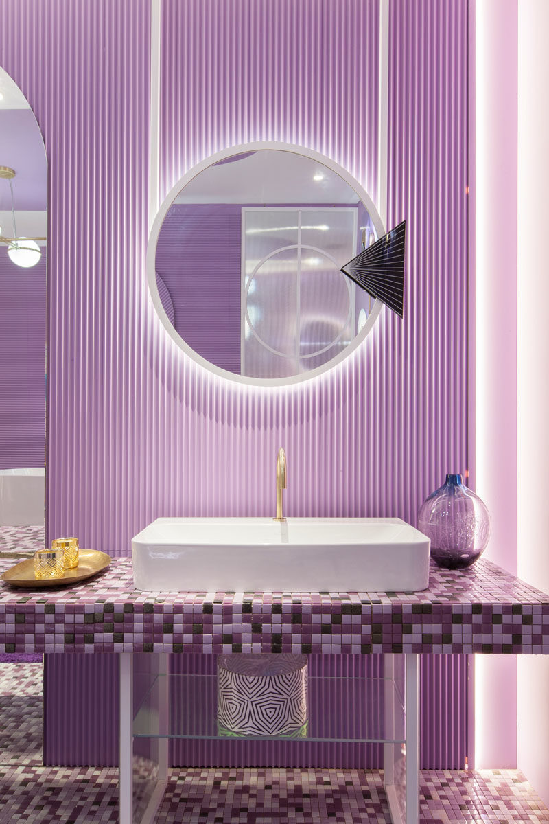Bathroom Ideas - A mosaic vanity in shades of purple sits below aluminum mirrors that are backlit to provide a soft glow and highlight the textured wall. #BathroomIdeas #BathroomDesign #PurpleBathroom #PurpleTiles