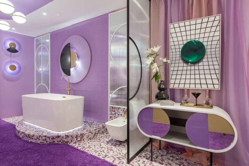 This purple hotel suite features a delicate glass partition that separates the bathroom from the bedroom. #Purple #PurpleInterior #PurpleBathroom