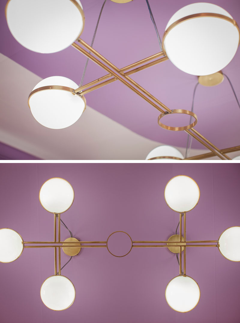 Bold lighting with a brass frame draws the eye upwards in this mostly purple hotel suite. #Lighting #LightingDesign
