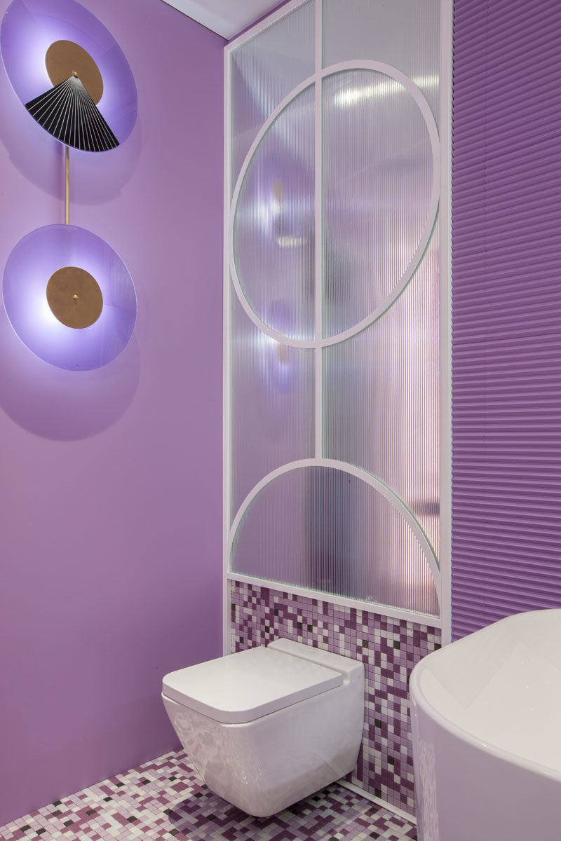 Decorative wall lighting provides an artistic accent in this modern hotel suite, where purple is the main color. #ArtisticLighting #LightingDesign