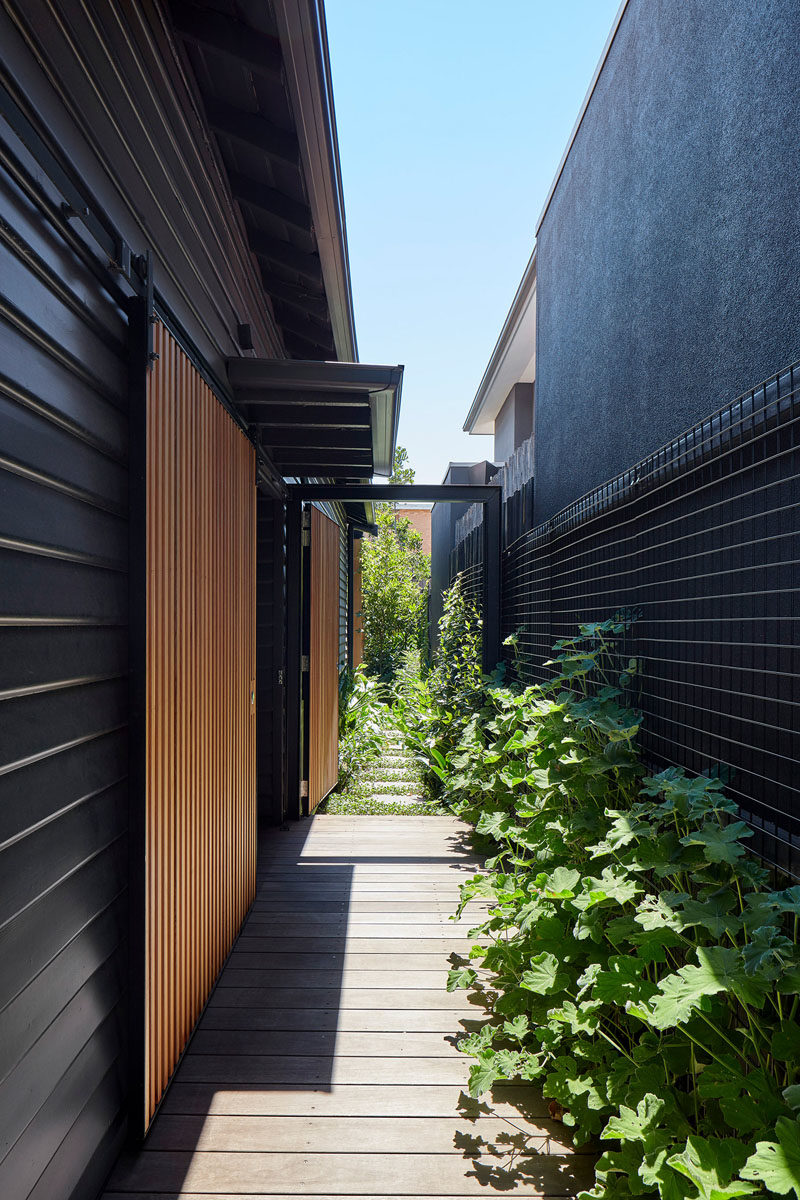 A ramp that runs down the side of this modern house, leads to the front door, and a stepping stone path continues to the backyard. #Ramp #Landscaping #BlackSiding