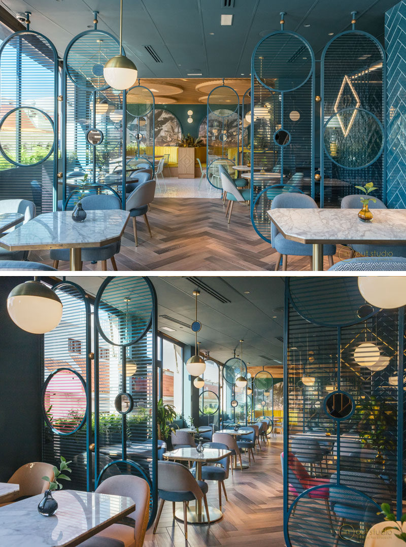 This modern restaurant features room dividers made from blue painted metal with circular cut-outs. The curved ends create a softer appearance, while the horizontal lines allow light to travel through them. #RoomDivider #RestaurantDesign #InteriorDesign #Screen