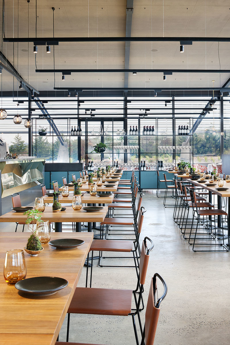Restaurant Ideas - In the casual dining area of this modern winery restaurant, solid wood tables are complemented by leather seating. #RestaurantDesign #RestaurantIdeas #InteriorDesign #HospitalityDesign #Winery