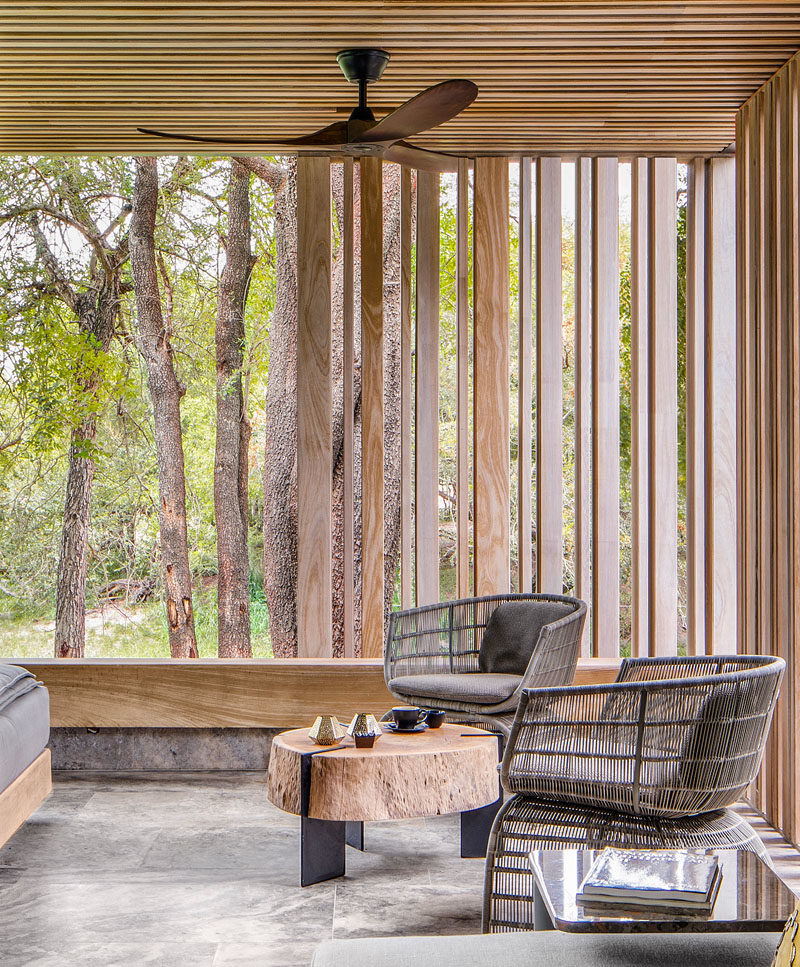 This outdoor sitting area is surrounded by wood slats that provide shade, and complement the trees outside. #SittingArea #WoodSlats
