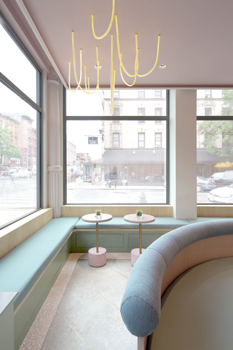 The modern gallery-like interior of this tea store, has light pink and blue accents, and features built-in benches that line the windows and walls. #TeaStore #InteriorDesign #Interiors #Cafe #Seating
