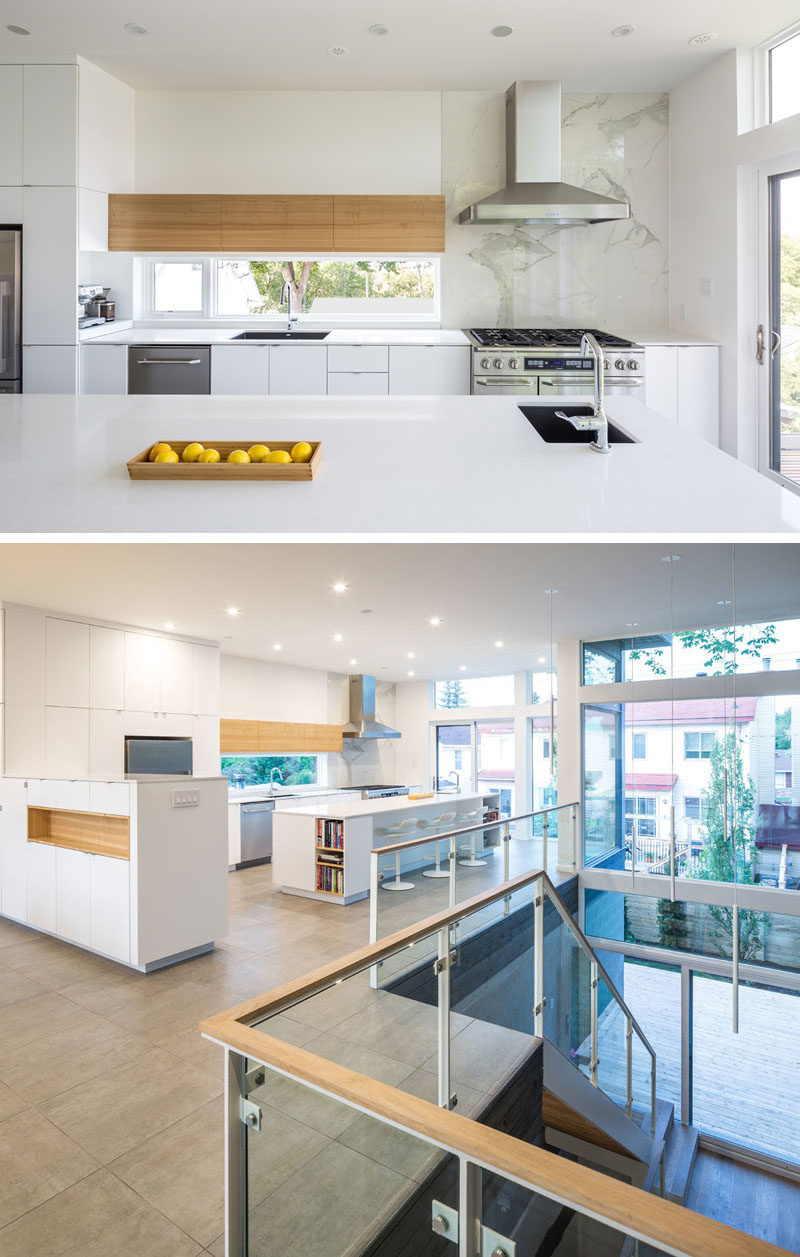 Kitchen Ideas - In this modern kitchen, minimalist white cabinets and light wood accents help keep the kitchen bright, while a sliding door opens to a balcony that overlooks the yard. #ModernKitchen #KitchenIdeas #WhiteKitchen