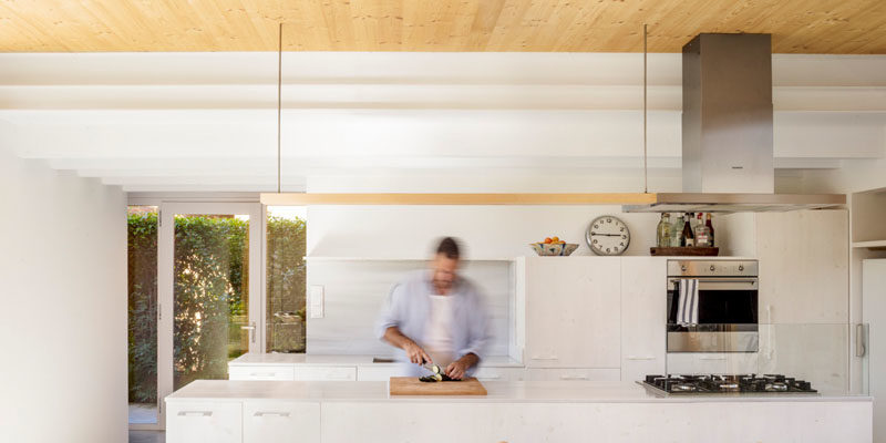 The wood ceiling in this modern house adds a natural touch to the all white kitchen. #KitchenDesign #WhiteKitchen