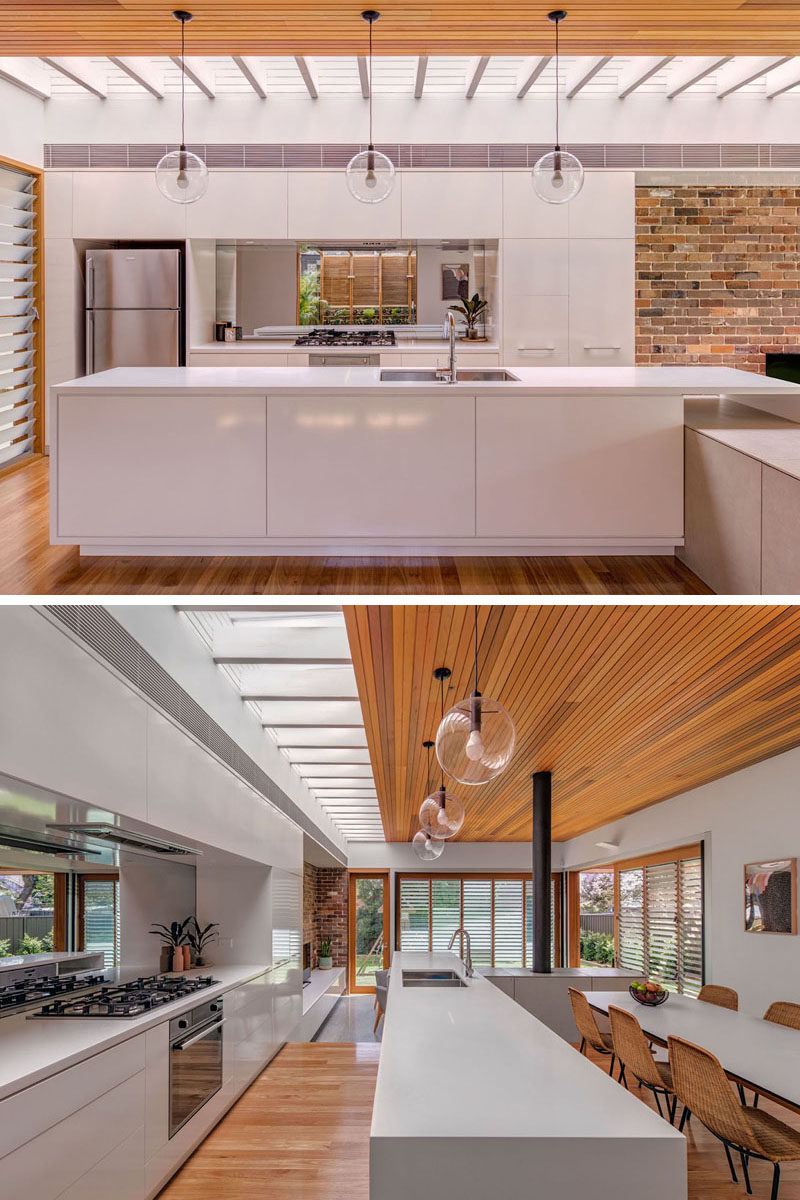 Kitchen Ideas - In this modern all-white kitchen, there's a skylight to add natural light, and a mirrored backsplash that reflects the herb garden outside. #KitchenIdeas #KitchenDesign #WhiteKitchen #KitchenSkylight #MirroredBacksplash