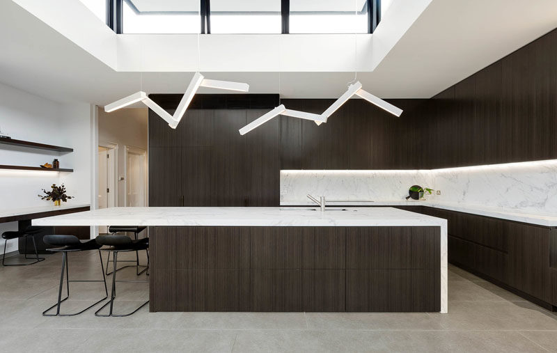 Kitchen Ideas - This modern kitchen has dark wood cabinets with light countertops, while a pair of lights draws the eye upwards to the clerestory windows. #KitchenIdeas #DarkKitchen #WoodKitchen #Windows