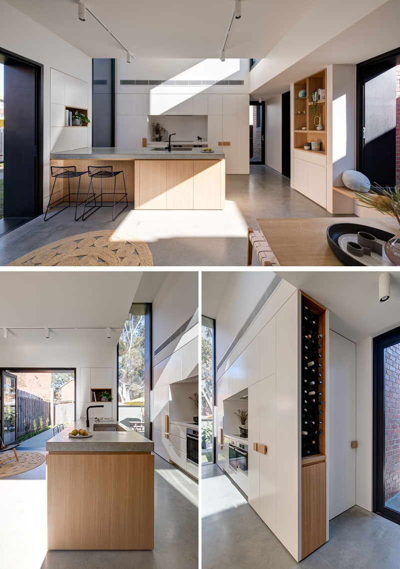 Kitchen Ideas - This modern kitchen has a large wood peninsula, minimalist white cabinets, and built-in wine storage. Behind the kitchen is a door that leads to the laundry room. #KitchenIdeas #ModernKitchen #KitchenDesign