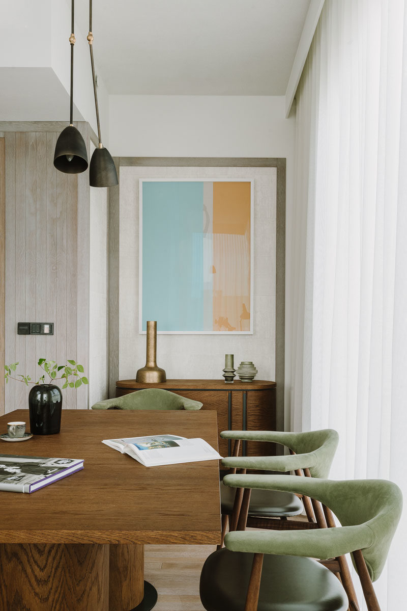 Dining Room Ideas - A large wood table is surrounded by soft green and wood chairs, while abstract wall art hangs above a small sideboard. #DiningRoomIdeas #DiningRoom