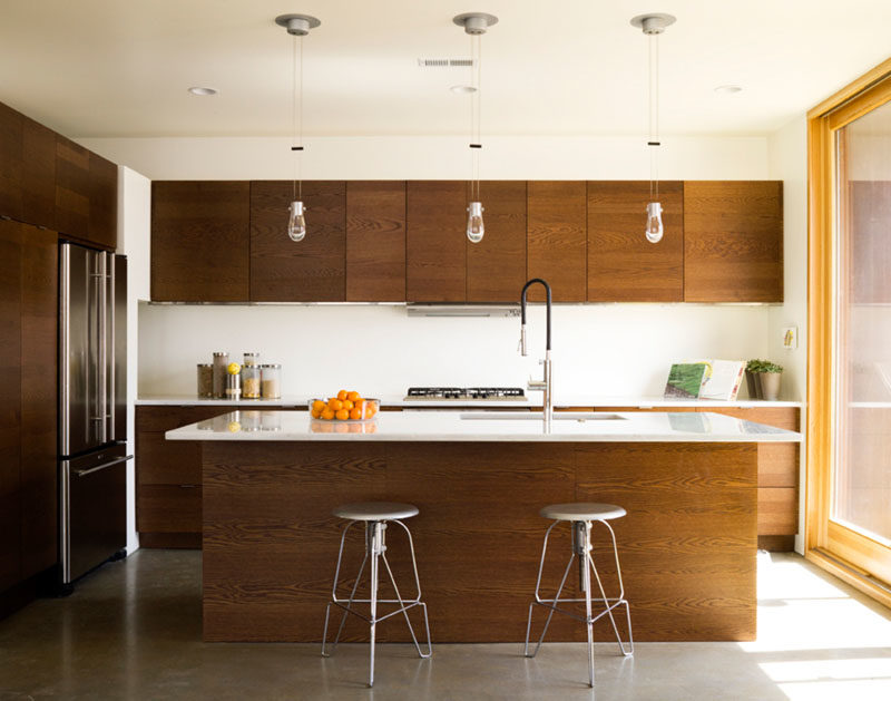 Kitchen Ideas - This modern kitchen with an island, has warm wood cabinets with white countertops and backsplash. #KitchenIdeas #KitchenDesign #WoodKitchen #ModernKitchen