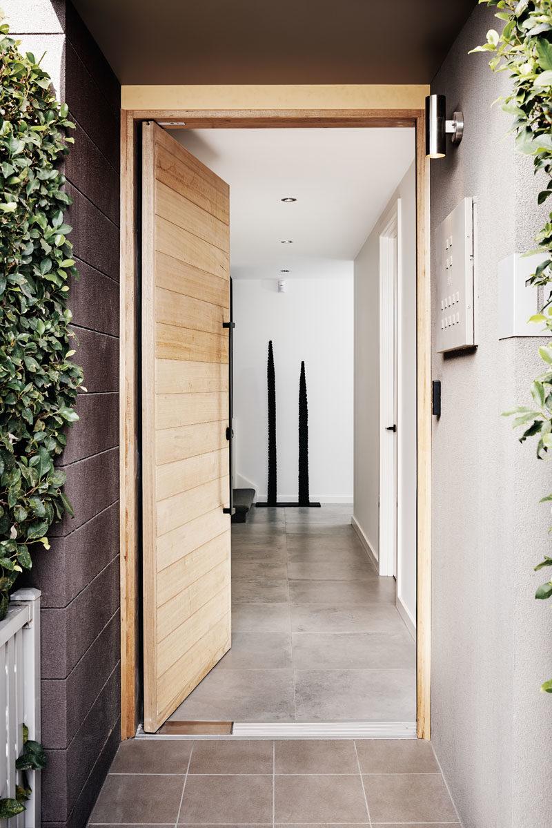 Door Ideas - This modern townhouse has a light wood front door that features a large modern black vertical handle. #ModernDoor, #DoorDesign #DoorIdeas #WoodDoor