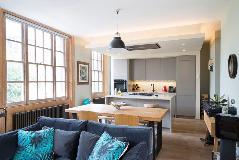 The interior of the building has received a bright update, with the main social areas of the house designed to take advantage of the large windows, while hidden lighting above the kitchen adds a warm glow to the room. #OpenPlan #Kitchen #LivingRoom #Dining #ModernInterior