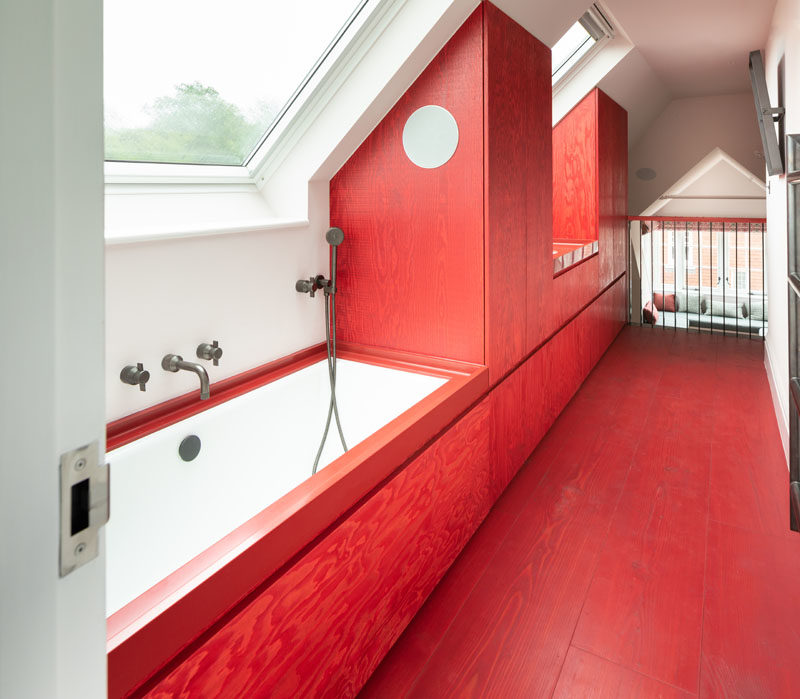Bathroom Ideas - This modern and bright red bathroom has an integrated Red Corian bathtub surround and sink, that complete the bold color block aesthetic. #RedBathroom #BathroomIdeas #ModernBathroom