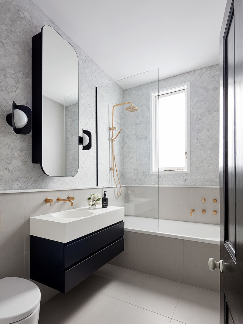 Bathroom Ideas - In this modern bathroom, a rounded rectangular mirror hangs above a small black and white vanity, while the black sconces complement the lower section of the vanity. Touches of gold add a glamorous touch to the space. #BathroomIdeas #ModernBathroom