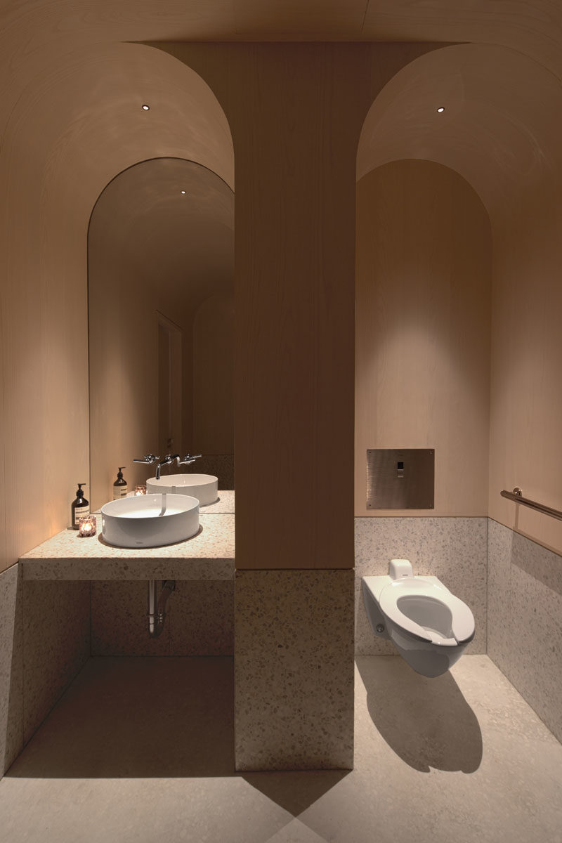 This modern tea store bathroom features an arched ceiling that helps to define the separate areas. #BathroomIdeas #BathroomDesign