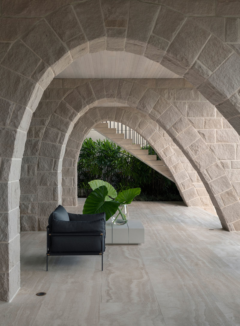 On the ground floor of this modern house, sandstone arches, lined timber ceiling boards, and travertine flooring form a powerful, tough, and muscular base to the home. #SandstoneArches #ModernHouse #ModernArchitecture #TravertineFlooring