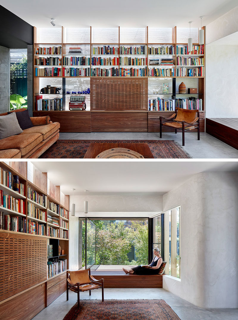 Living Room Ideas - In this modern living room, a wall of shelving surrounds a television, that's hidden from view with a perforated panel. A built-in window seat with a large pivoting window, is the perfect place to read a book and look out to the rear yard. #LivingRoom #HiddenTV #WindowSeat #PivotingWindow #Shelving