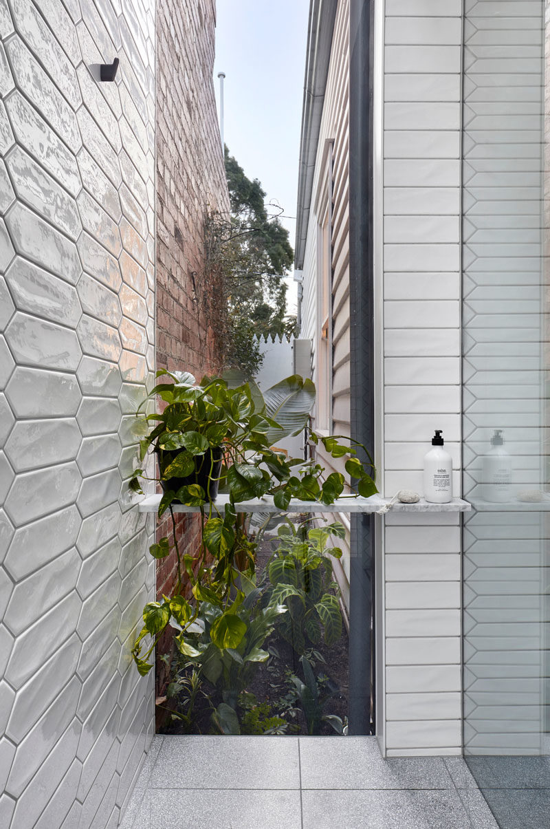 Bathroom Ideas - In this modern white bathroom,  white picket tiles cover the walls, and in the shower, a floor-to-ceiling window with views of a tiny garden at the side of the house. #BathroomIdeas #PicketTiles #WhiteTiles #Windows