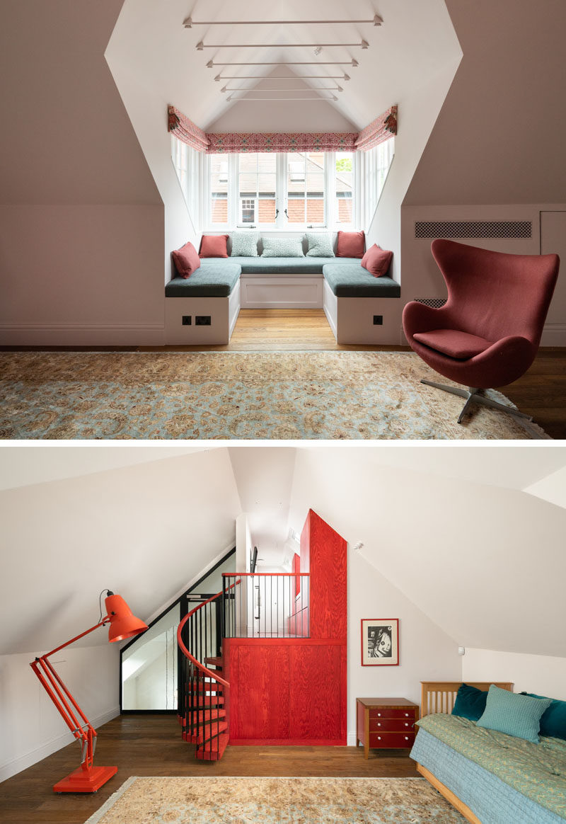 A recessed window bench seat has been added to this open room offering a peaceful spot for reading and reflection. On the opposite wall is a bright red accent wall with a spiral staircase. #WindowSeat #WindowBench #InteriorDesign #SpiralStairs