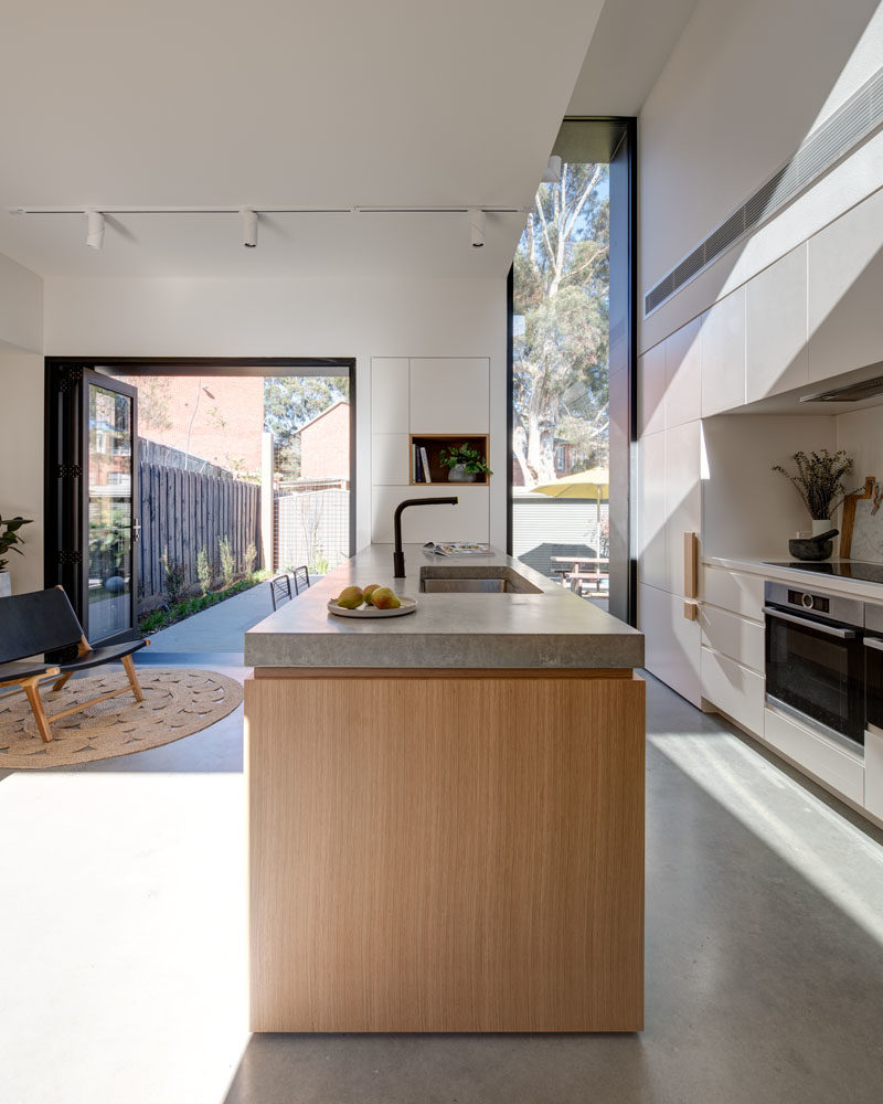 Kitchen Ideas - This modern kitchen has a large wood peninsula, minimalist white cabinets, oversized hardware, and built-in wine storage. Behind the kitchen is a door that leads to the laundry room. #KitchenIdeas #ModernKitchen #KitchenDesign