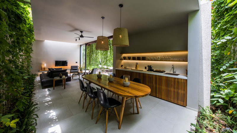 This modern villa has a kitchen with hidden lighting, and green walls that add a touch of nature. #Kitchen #DiningRoom #GreenWalls