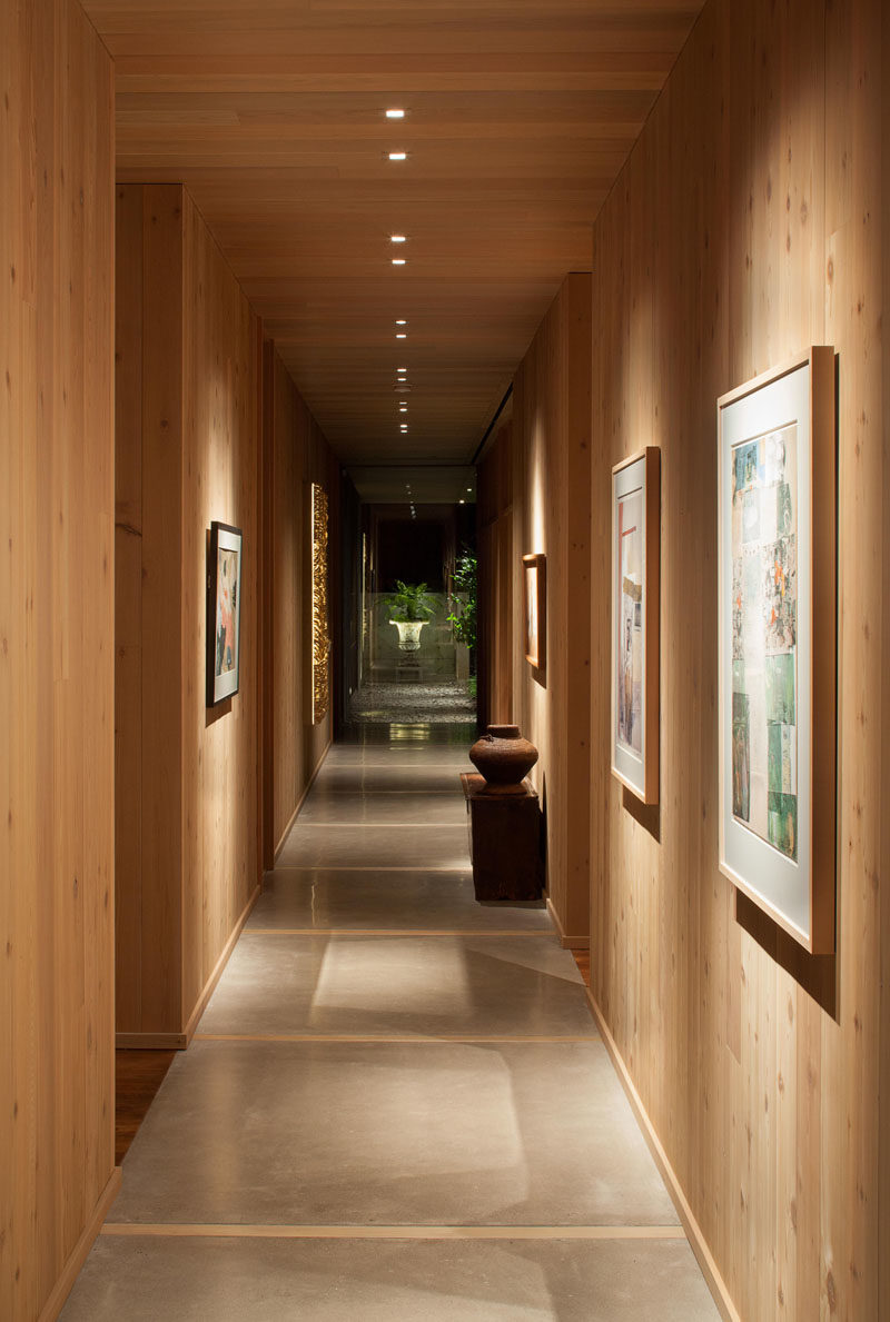 "In this contemporary house, a long gallery hallway lined in wood, separates the private bedroom spaces from the more ""public"" living spaces, and showcases the owners' artworks.  #Hallway #InteriorDesign"