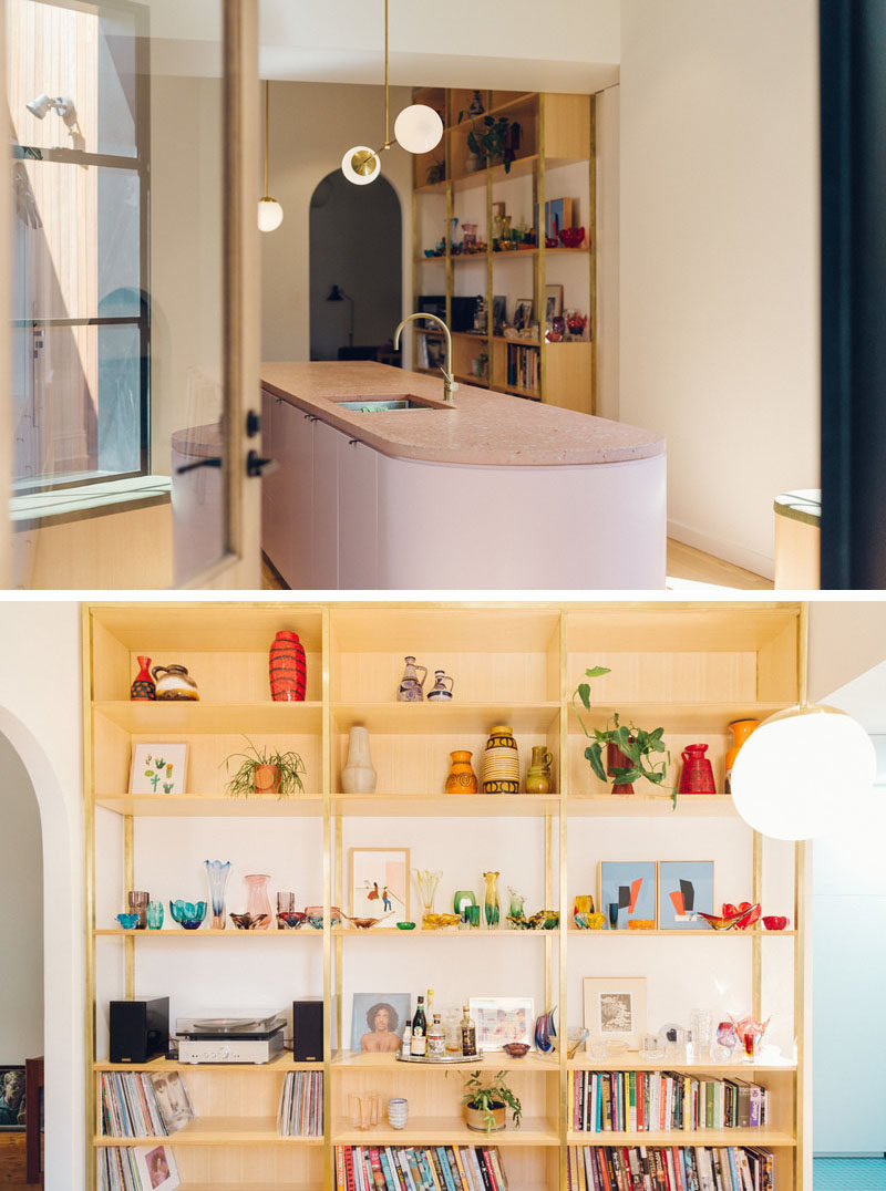 Shelving Ideas - A wood shelving unit runs alongside the dining area, and provides a place for the home owners' collection of unique Italian and Czech glassware, books, and German Pottery. #ShelvingIdeas #WoodShelving #Bookshelf