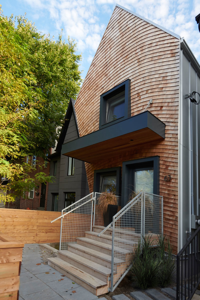 House Design Ideas - This curved house combines wood shingles and black accents for a modern appearance. #Shingles #ModernHouse #BlackWindowFrames #HouseDesignIdeas #CurbAppeal