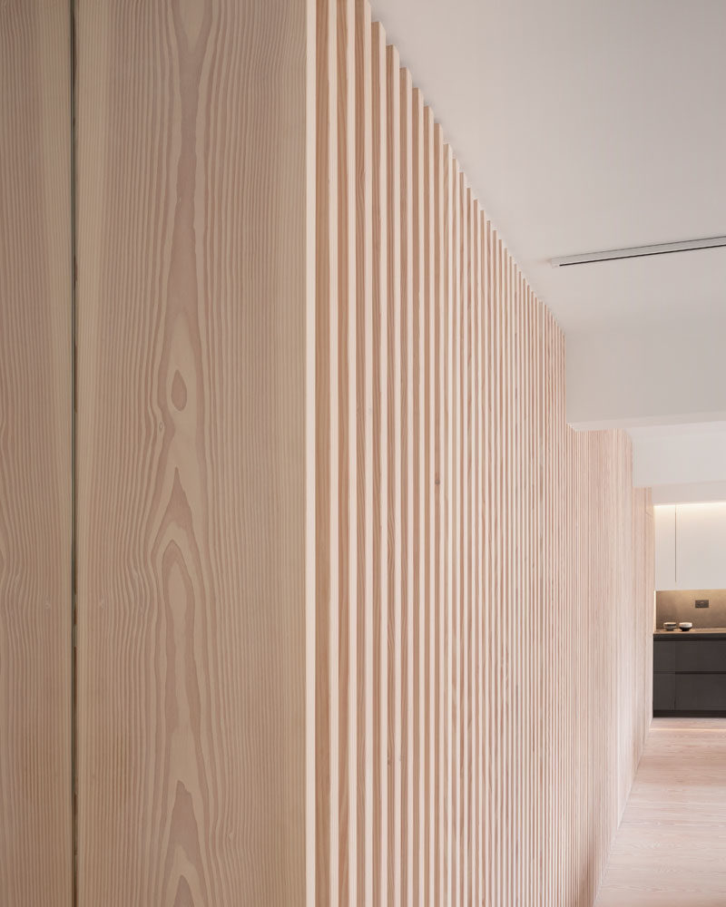 Interior Design Ideas - The wood slat wall in this modern apartment incorporates secret doors, and all storage and service requirements for the apartment, including kitchen appliances and hanging cupboards, resulting in a highly efficient plan. #InteriorDesignIdeas #WoodSlatWall #HiddenAppliances #HiddenFridge #IntegratedFridge #HiddenStorage #SecretDoors #HiddenDoors