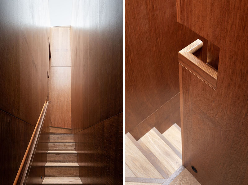 Staircase Ideas - This modern staircase clad in Brown Oak wraps itself up behind the library, forming a distinctive space, lit by the full length skylight above. Recessed LED lighting guides the occupants up to the second story of the library, and highlights the careful craftsmanship of the integrated handrail. #StairIdeas #HandrailIdeas #Staircase #Handrail #BuiltInHandrail